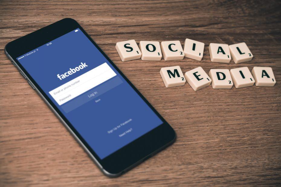 Mobile phone showing Facebook, scrabble letters spelling social media